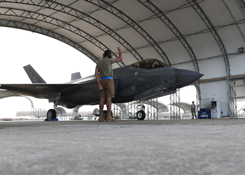 U.S. Air Force Airman 1st Class Jaivon Bland, 33rd Aircraft Maintenance squadron F-35A Lightning II dedicated crew chief, signals to the pilot during prelaunch procedures at Eglin Air Force Base, Florida, Aug. 26, 2020. The 33rd AMXS introduced a shorts uniform to help combat hot weather conditions on the flightline. (U.S. Air Force photo by Airman 1st Class Amber Litteral)