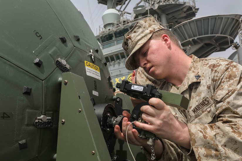 A Marine examines a satellite component