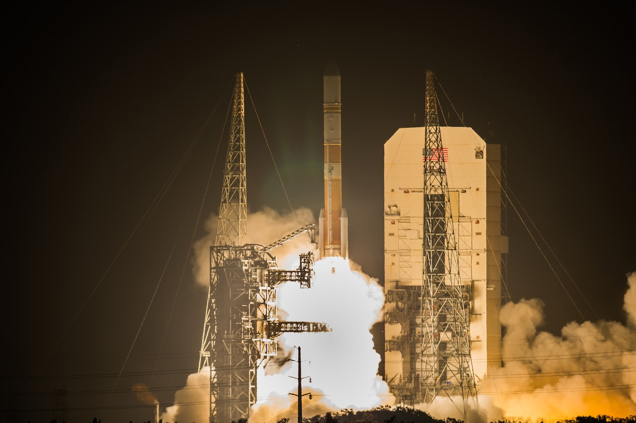A rocket launches from the launchpad at night.