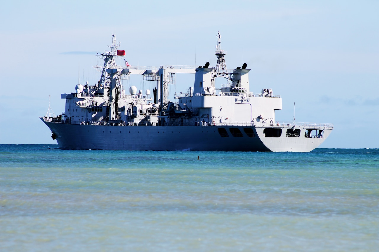 A large military vessel moves through the ocean.