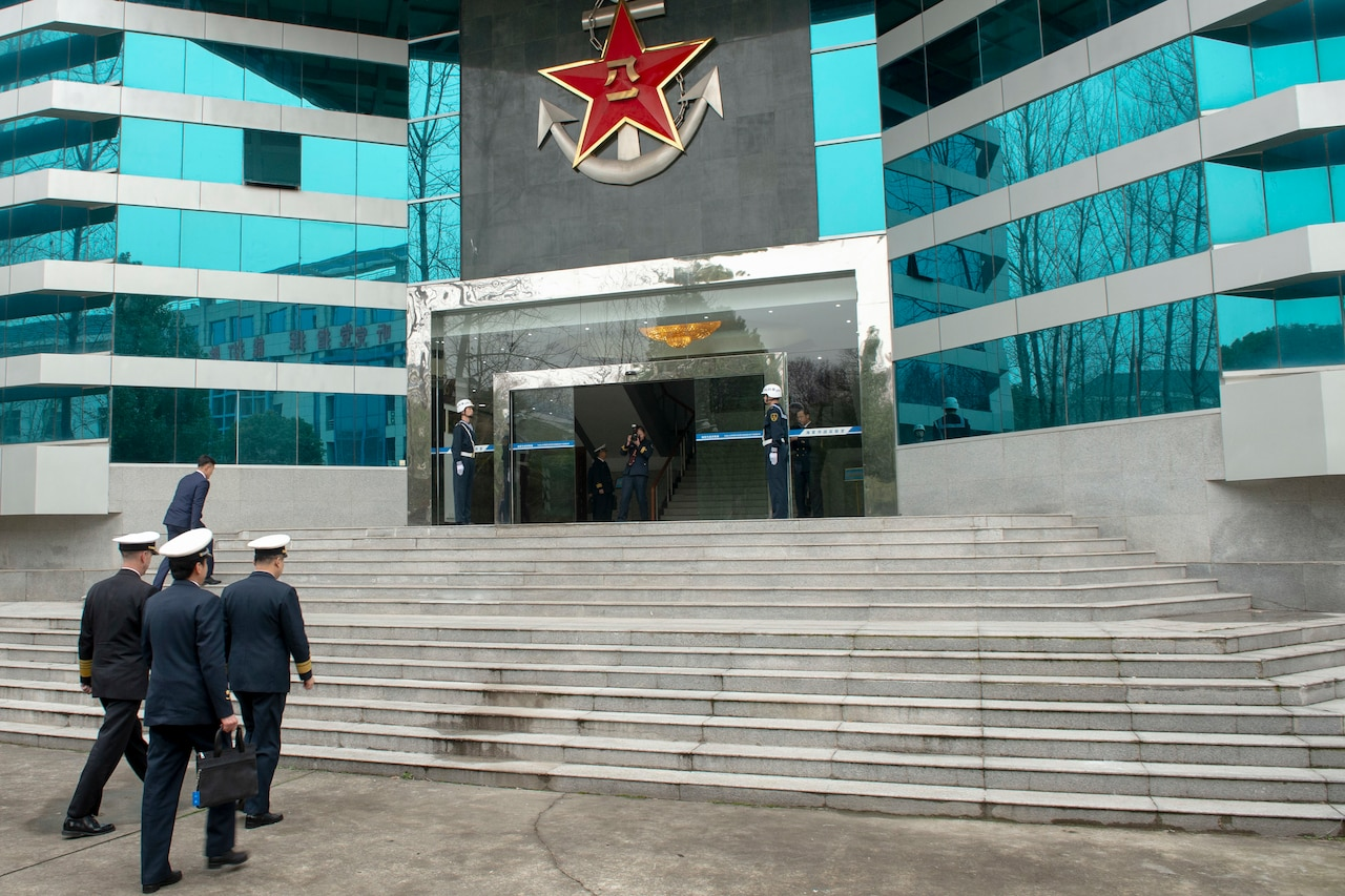 Men in military uniforms approach steps in front of a building.