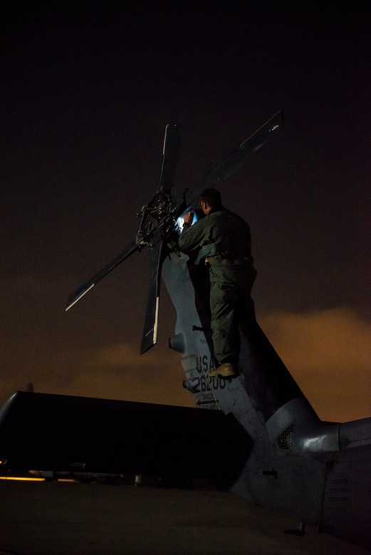 a photo of an airman on the tail of an HH-60