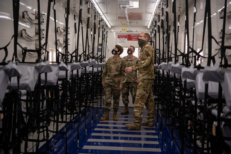 Three military members walk along a hallway with hanging seats