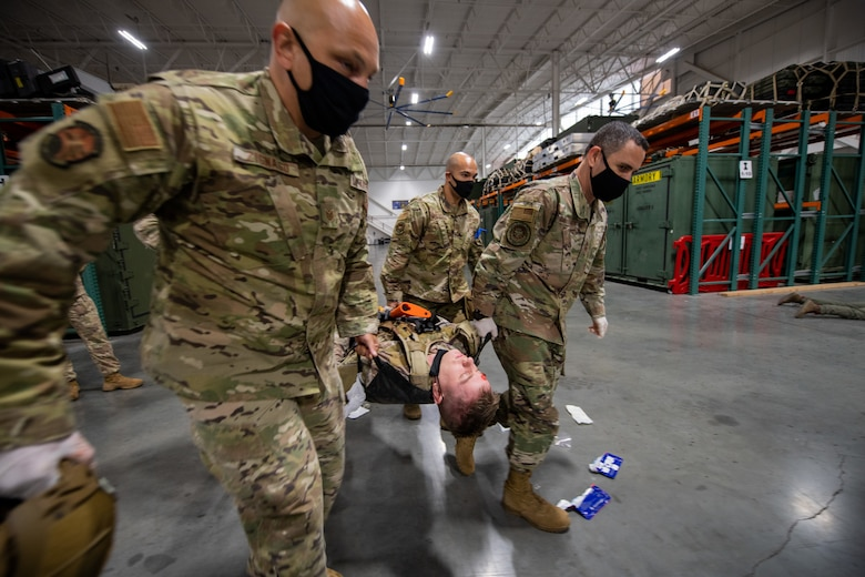 Three military members help to hand-carry a fourth on a stretcher inside of a warehouse with fluorescent lights