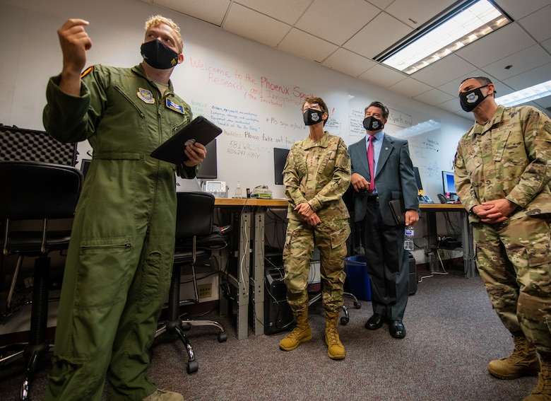 Military members and one man in a suit stand inside a room with fluorescent lights and a carpeted floor. They are all wearing masks.