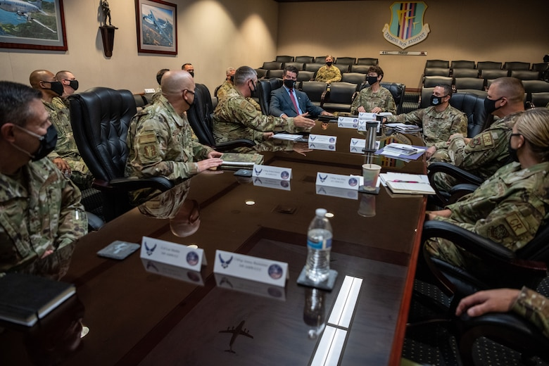 Military members sit in a conference room around a long table.