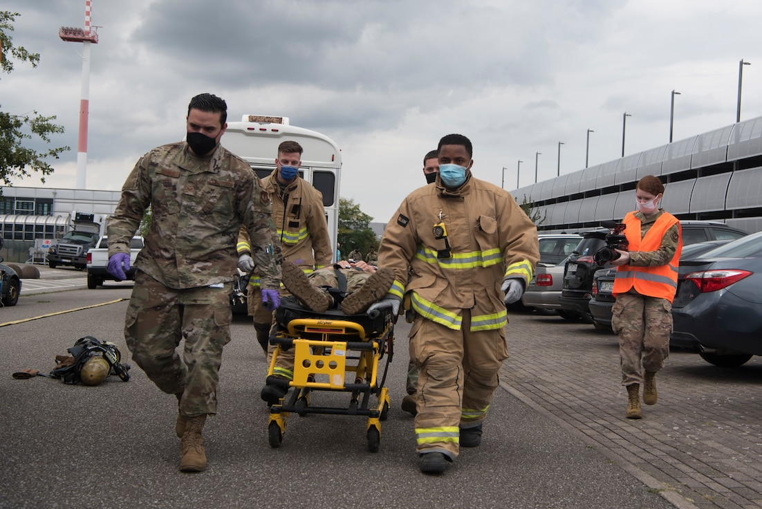 Airmen escort injured victim to ambulance.