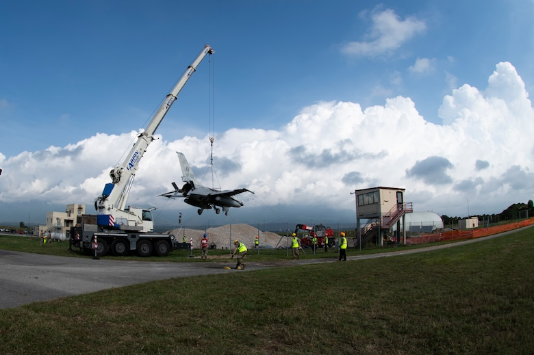Airmen from the 31st Maintenance Squadron and 52nd MXS work together to relocate an F-16 Fighting Falcon during a training event at Aviano Air Base, Italy, Aug. 29, 2020.  The purpose of this training is to prepare Airmen to quickly remove an aircraft from the runway during a real world event. (U.S. Air Force photo by Senior Airman Caleb House)
