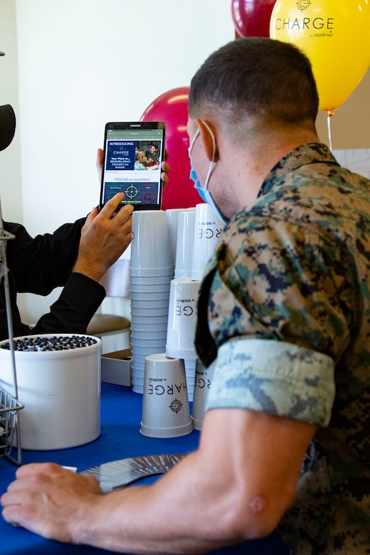 Allen Wolff, left, an information technology specialist for Sodexo, guides a U.S. through the set up process of the newly released mobile app, Charge by Sodexo, during the app's launch event at the French Creek 65 Mess Hall on Marine Corps Base Camp Lejeune, North Carolina, Aug. 24, 2020. Charge by Sodexo is a free mobile app available on the Google Play Store and Apple App Store and features mess hall searching capability through geo-location or installation name and mess hall number which allows users to view local menus for specialty bars, caloric intake information, nutrition facts and feedback.  (U.S. Marine Corps photo by Lance Cpl. Ginnie Lee)