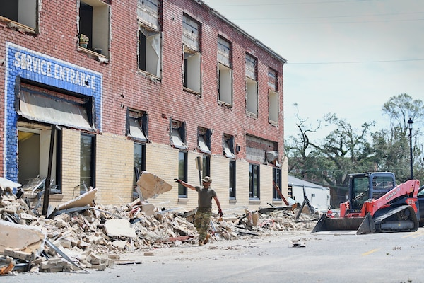 Airmen from the 159th Civil Engineering's Debris Clearance Package clear rubble from a road in downtown Lake Charles, Louisiana, Aug. 30, 2020. The Louisiana Air National Guard Airmen arrived with heavy equipment after Hurricane Laura's landfall to clear roadways of the hardest-hit areas in and round Calcasieu Parish.
