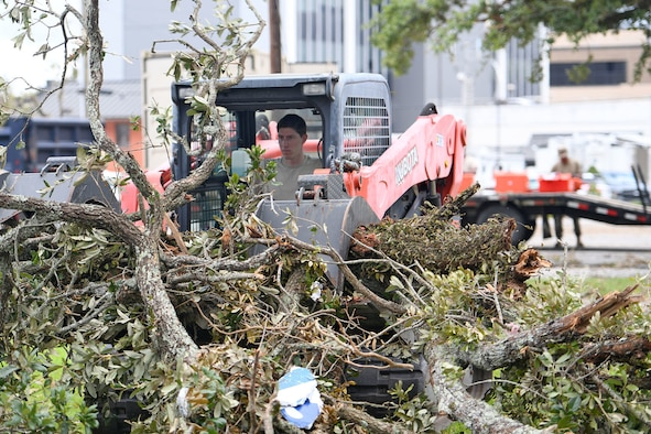 Louisiana National Guard Senior Airman William Bommer, 159th Civil Engineering Squadron's heavy equipment journeyman,  removes tree branches in downtown Lake Charles, La., Aug. 30, 2020, after Hurricane Laura caused heavy damage in the area.