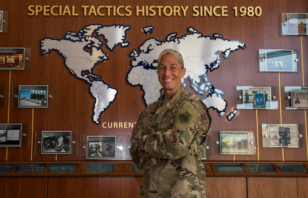 """Colonel Black stands in front of a map of the world titled """"Special Tactics History since 1980."""""""