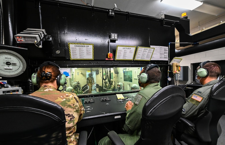 Three aerospace physiology specialists from the 14th Operational Medical Readiness Squadron observe as student pilots from the 23rd Flying Training Squadron at Fort Rucker, Alabama conduct hypobaric chamber training on August 21, 2020, at Columbus Air Force Base, Miss. The chamber provides a training system which replicates the effects of barometric pressure change on the human body. (U.S. Air Force photo by Airman 1st Class Davis Donaldson)