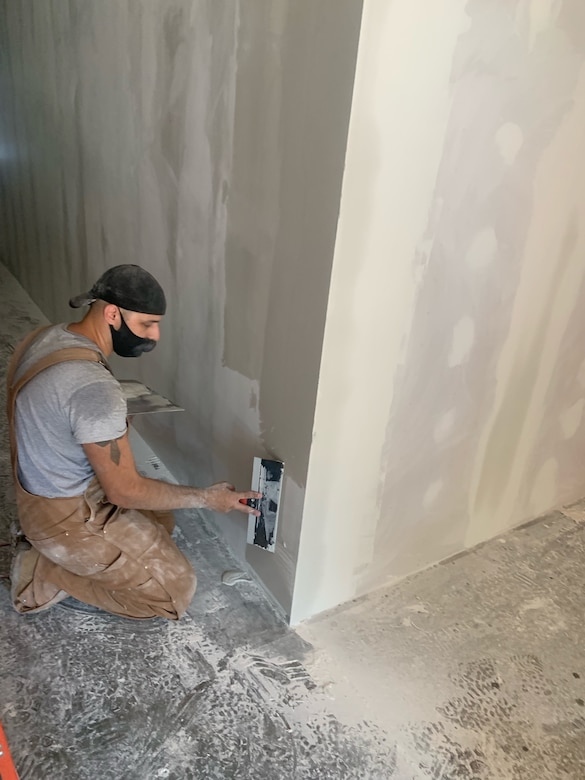 Worker sits on floor making repairs to hole in a wall.