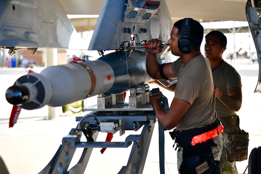a photo of a weapons load crew