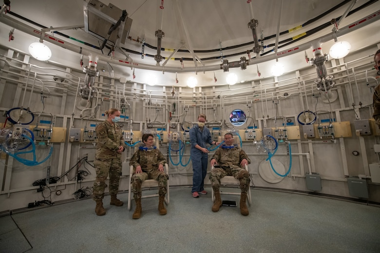 Three military members sit inside a large, circular room with a medic. All are wearing face masks. There are pipes and valves on the white walls.