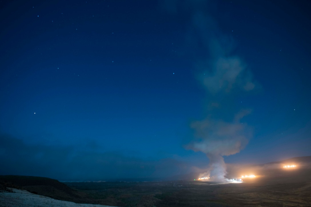 Lights and a plume of smoke can be seen against a dark sky.