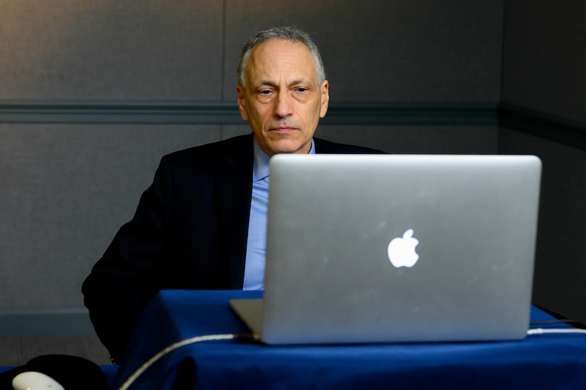 A man sits in front of a laptop.