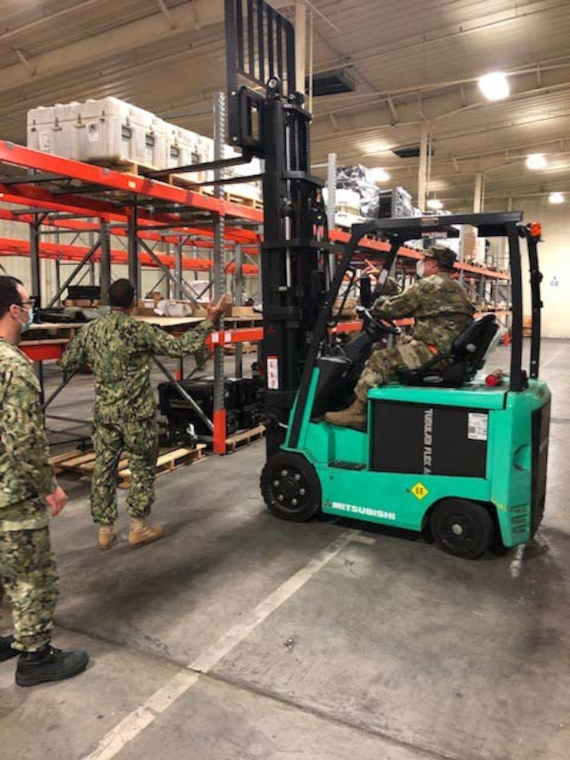 Navy Petty Officer 1st Class Jesus Martinez, left, observes as Army Staff Sgt. Derek Grudzieski guides Army Sgt. Bobby Wright in forklift operation during a mid-July annual reserve training assignment in support of the DLA Disposition Services site at Warner Robins, Georgia.