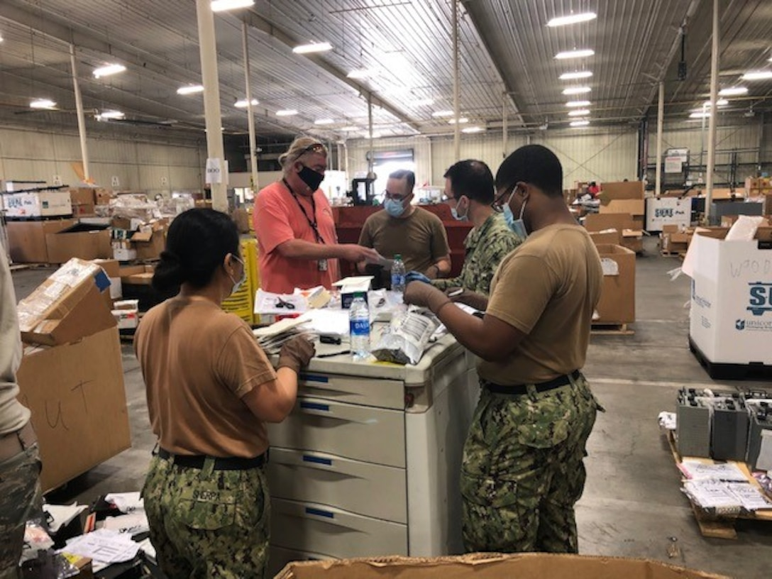 """Navy Petty Officer 2nd Class Lobsang Sherpa, far left, aids DLA Disposition Services employee Thomas """"CJ"""" Czerniejewski, along with Chief Petty Officer Cesar Acosta, Petty Officer 2nd Class Gordon Cahoone and Seaman Apprentice Joseph Deramus as they attack the backlog of received items at the DLA Disposition Services site at Warner Robins, Georgia."""