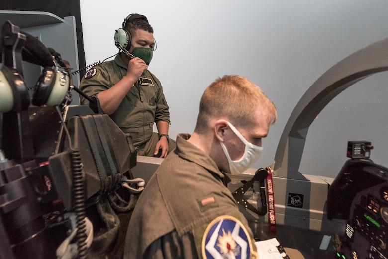 "Senior Airman Brenten Boler, 47th Operations Group T-6 simulator instructor, works with 2nd Lt. Chris Summins, 47th Student Squadron student pilot, as he prepares for a flight in the T-6A Texan II simulator, August 31, 2020, at Laughlin Air Force Base, Texas. ""I value the job I have now because it gives me the opportunity to pass on the knowledge that I have as a military aviator, as well as an opportunity to work on my own skills and improve my understanding of concepts by teaching them to curious students,"" Boler said. ""I find the work as an instructor to be incredibly rewarding and enjoy working with the student pilots to help them develop their understanding and skills."" (U.S. Air Force photo by Senior Airman Anne McCready)"