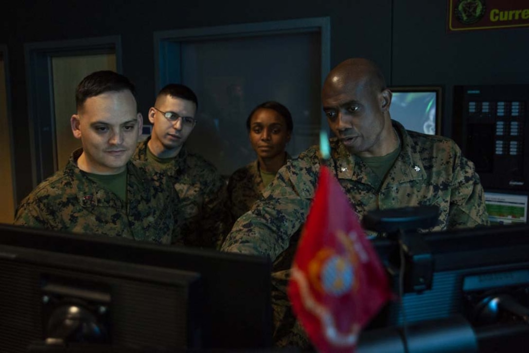 Four Marines look at a computer monitor.