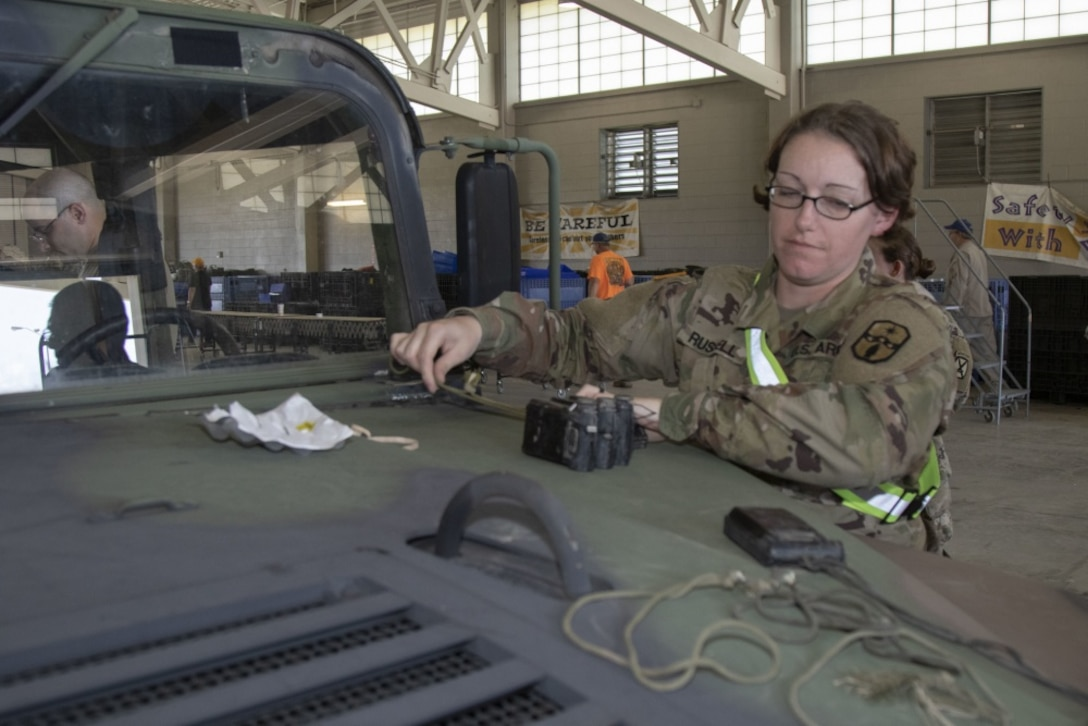 A female service member looks at some equipment that sits on the hood of a military vehicle.