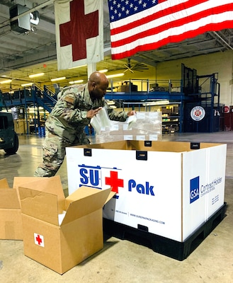 Tech. Sgt. Brison King, non-commissioned officer in charge, Warehouse Operations, Joint Base San Antonio-Lackland, packs critical lab supplies at Port San Antonio, Texas, August 24, 2020.