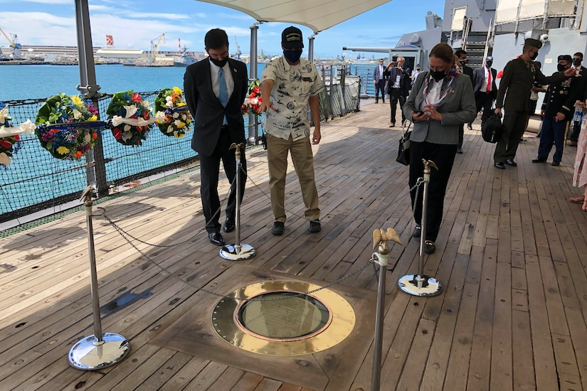 Three people examine a plaque set into the deck of a ship.