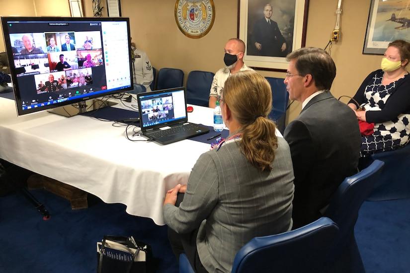 Two people speak to World War II veterans via a computer.