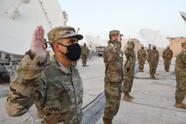 Airmen deployed to Al Udeid Air Base, Qatar, raise their right hands during an enlistment ceremony as they transferred into the Space Force on Sept. 1, 2020. The Space Force is the United States' newest service in more than 70 years. (U.S. Air Force photo by Staff Sgt. Kayla White)