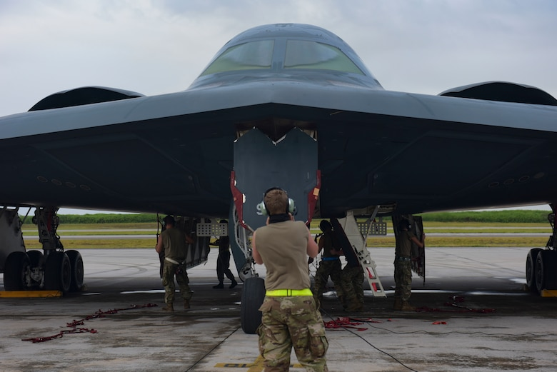 A U.S. Air Force maintainer assigned to the 393rd Expeditionary Bomb Squadron, Whiteman Air Force Base, Missouri, talks to the pilots of a B-2 Spirit Stealth Bomber at Naval Support Facility Diego Garcia, to support a Bomber Task Force mission, Aug. 14, 2020. As part of their BTF deployment, the B-2s participated in a combined United States-Australia exercise with Marine Rotational Force -Darwin and Australian Defence Forces. During the exercise, MRF-D and ADF Joint Terminal Attack Controllers coordinated airstrikes with U.S. Air Force B-1B Lancers and B-2 Spirit Stealth Bombers. (U.S. Air Force photo by Senior Airman Alexandria Lee)
