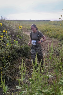 Sgt. Ayrin Hammer-Ripperger, Iowa Army National Guard, runs through brush and wildflowers, Aug. 30, 2020, at the Greenlief Training Site, near Hastings, Nebraska, during the inaugural All Guard Endurance Team time trials.