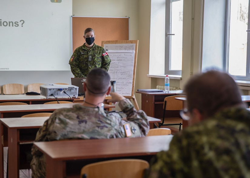 Canadian Forces Capt. Samantha Wall listens intently as United States Army Maj. Andrew Ward poses a question during an exercise design course, Aug. 28 at Combat Training Center-Yavoriv, Ukraine.