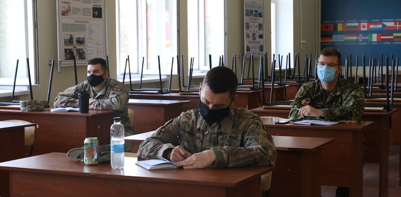 U.S Army Maj. Andrew Ward, Task Force Illini JELC Chief takes notes during Canadian Forces Capt. Samatha Wall's course on exercise design, Aug. 28 at Combat Training Center-Yavoriv, Ukraine.
