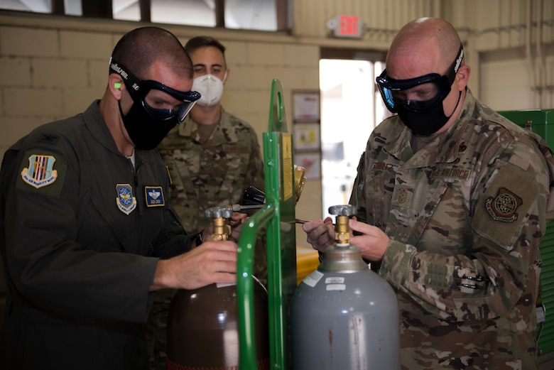 U.S. Air Force Col. Zachery Jiron, left, 60th Air Mobility Wing vice commander, and Chief Master Sgt. Robert Schultz, right, 60th AMW command chief, remove the caps off liquid oxygen bottles while Senior Airman Peter Gatsios, 60th Maintenance Squadron aircraft electric and environmental systems journeyman, guides them during Leadership Rounds Aug. 28, 2020, at Travis Air Force Base, California. The Leadership Rounds program provides 60th AMW leadership an opportunity to interact with Airmen and get a detailed view of each mission performed at Travis AFB. (U.S. Air Force photo by Senior Airman Cameron Otte)