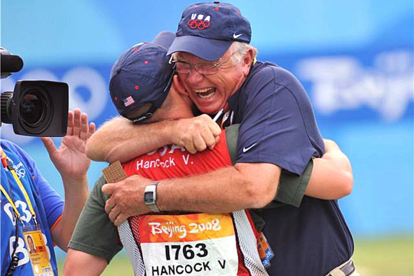 An older man hugs a man wearing a vest with the words Beijing 2008 Hancock V. USA.