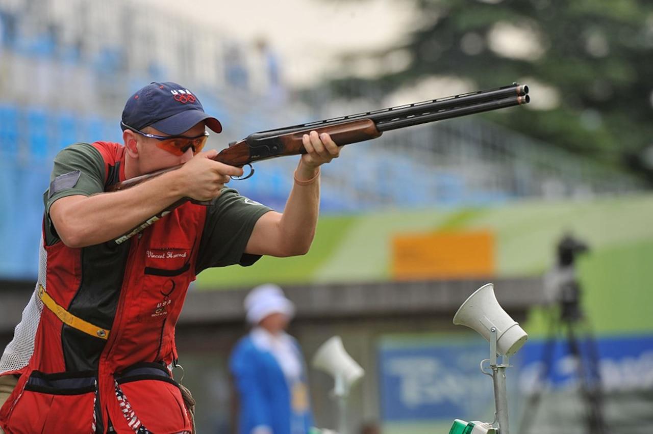 A man aims a shotgun.