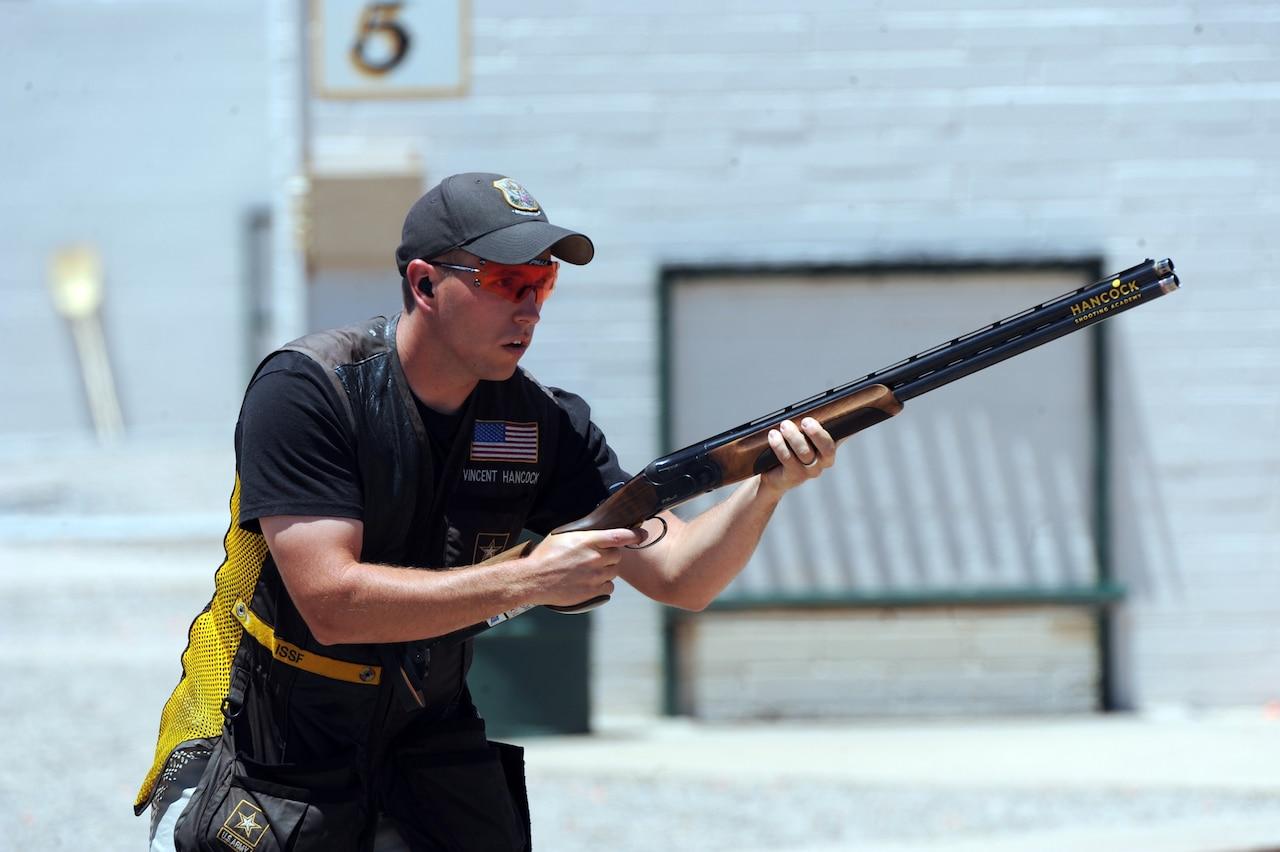 A man holds a shotgun.