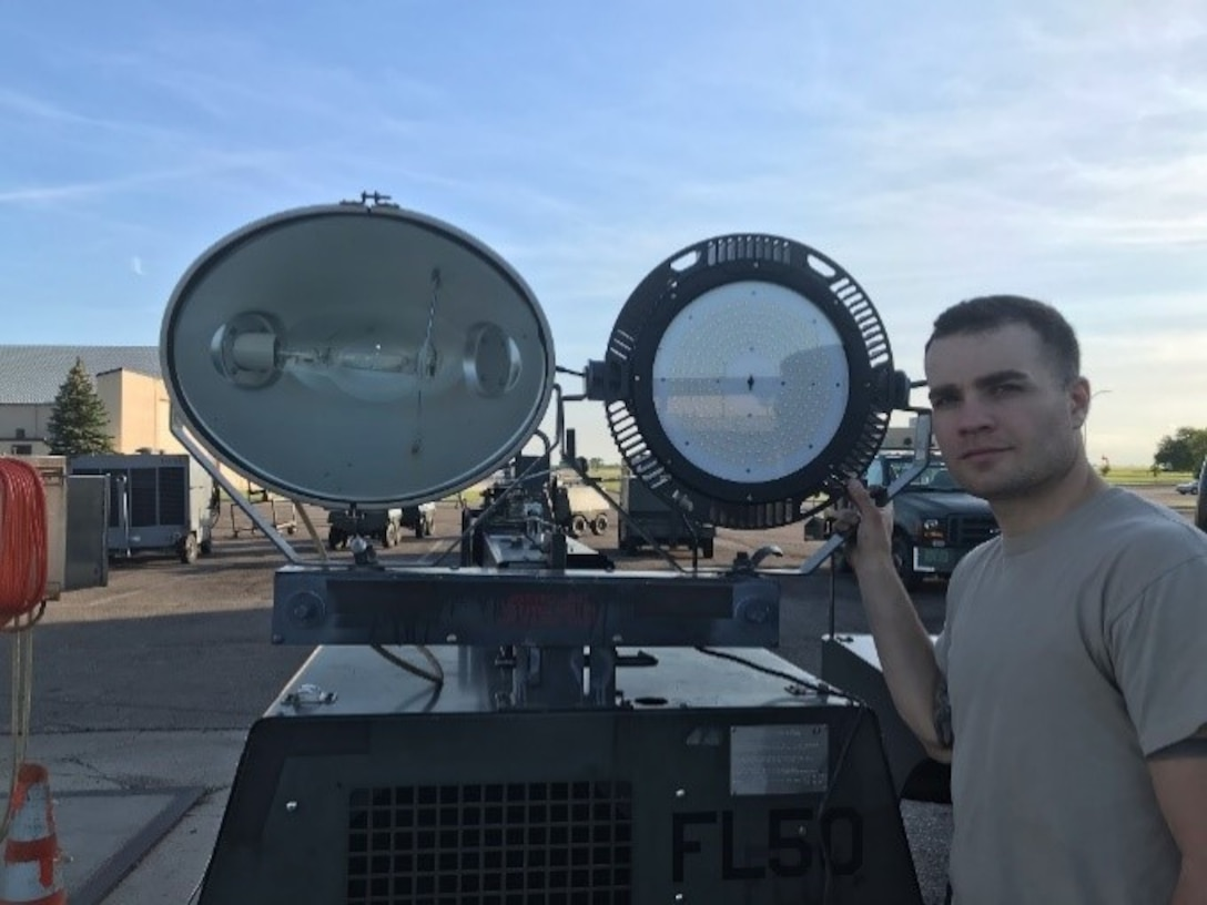 Senior Airman Matthew Brown, Minot 5th Maintenance Squadron AGE Flight, compares a legacy metal-halide lamp with a new LED fixture. (U.S. Air Force photo/Master Sgt. Miguel Alvarez)
