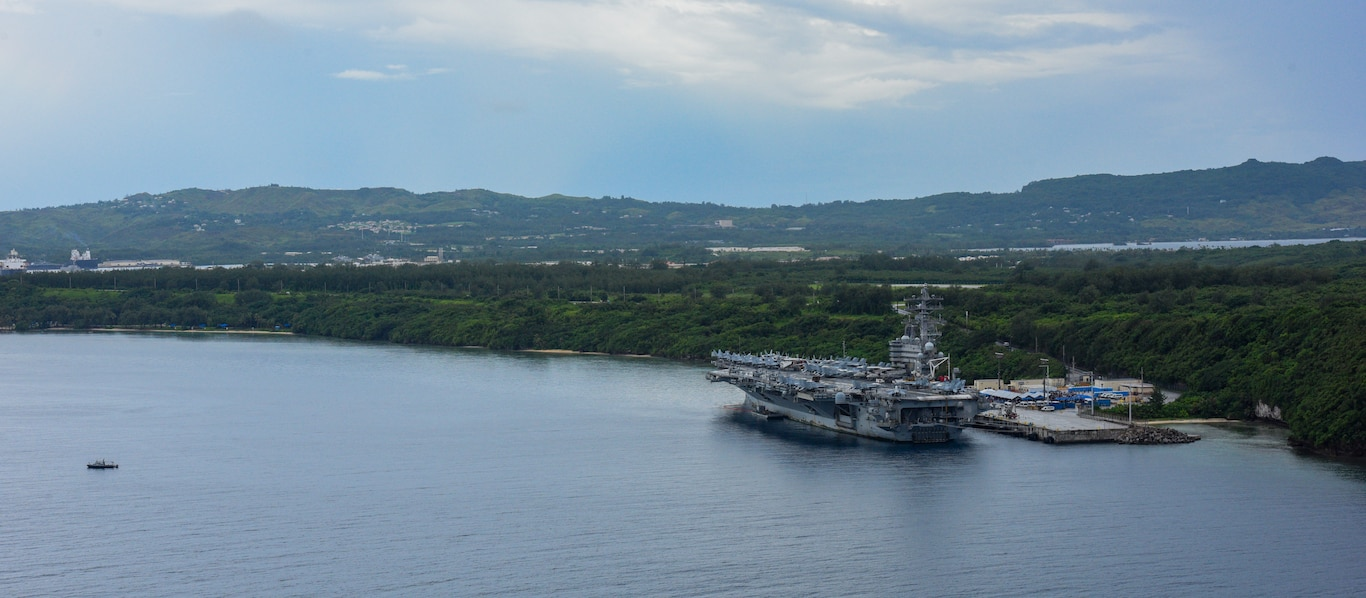 An aerial view of U.S. Naval Base Guam (NBG) shows aircraft carrier USS Ronald Reagan (CVN 76) moored in Apra Harbor.