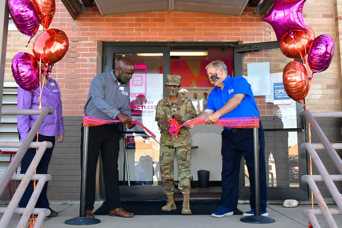 (Left to right) Edward James, Hill Exchange acting general manager, Col. Jenise Carroll, 75th Air Base Wing commander, and George Hart, Dunkin' and Baskin-Robbins franchisee, cut the ribbon in front of Dunkin' Donuts and Baskin-Robbins.