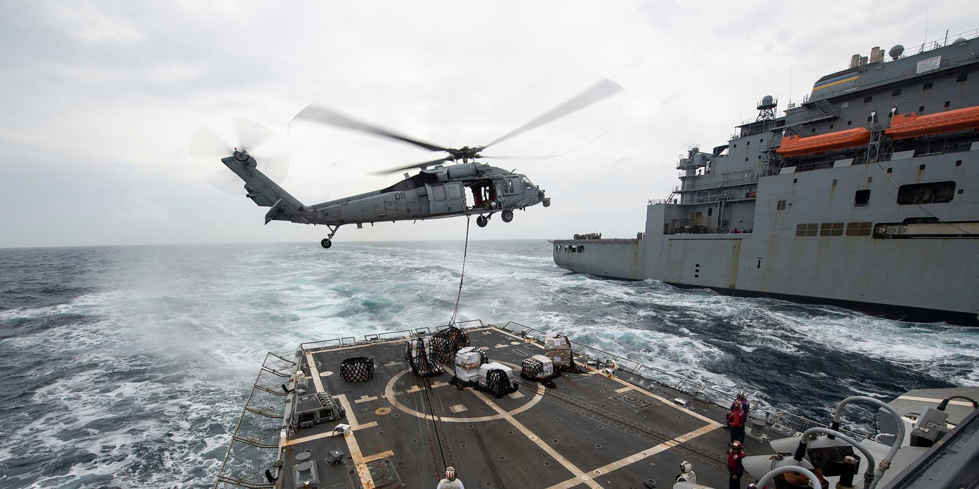 "A U.S. Navy MH-60S Sea Hawk, assigned to the ""Island Knights"" of Helicopter Sea Combat Squadron (HSC) 25, drops off cargo on the flight deck of the Arleigh Burke-class guided-missile destroyer USS Rafael Peralta (DDG 115) during a replenishment-at-sea with the Military Sealift Command dry cargo ammunition ship Alan Shepard (T-AKE 3)."
