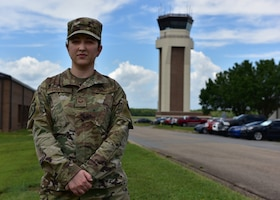 A woman in the operational camouflage pattern uniform stands in front of a tower.