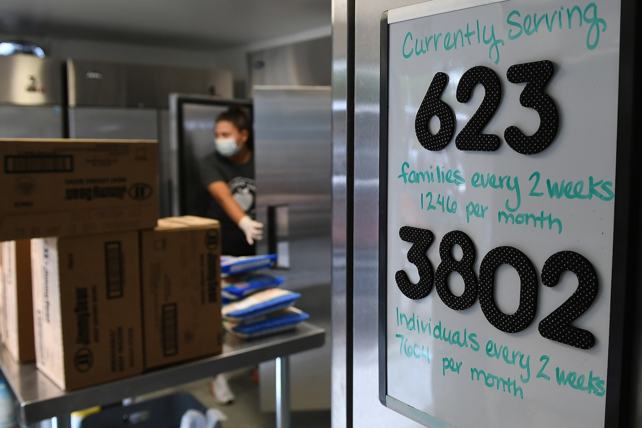 A white board shows the number of families served by a food bank as a woman works in the background.