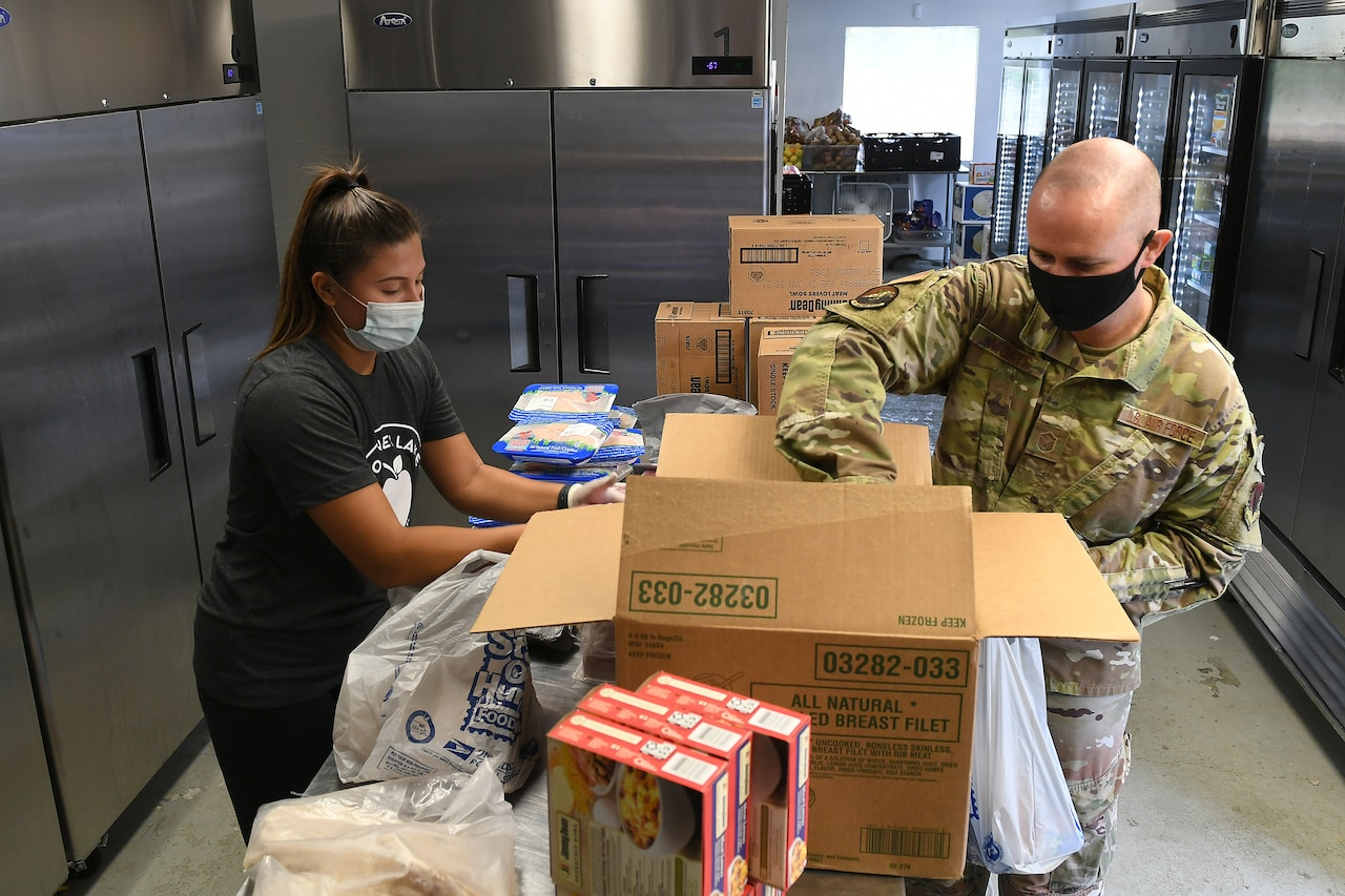A service member and a woman wearing a food bank tee shirt pack a box with food.