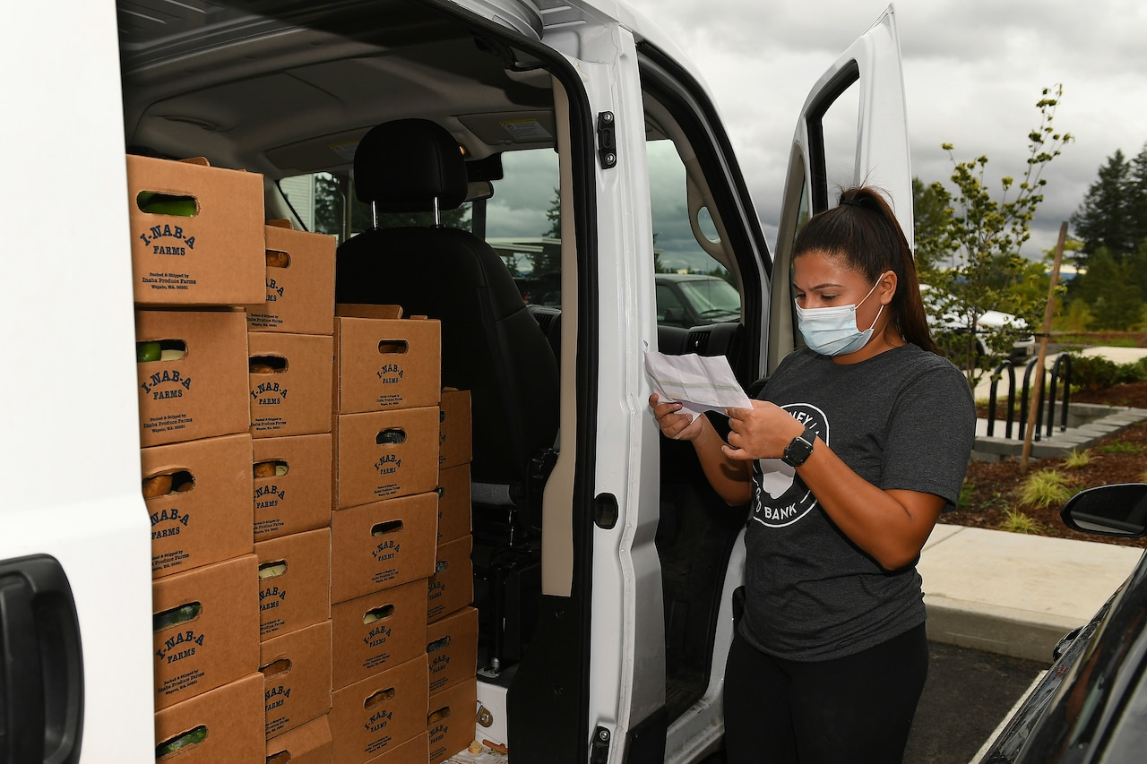 A woman wearing a food bank shirt prepares to remove a box of food from a packed vehicle.