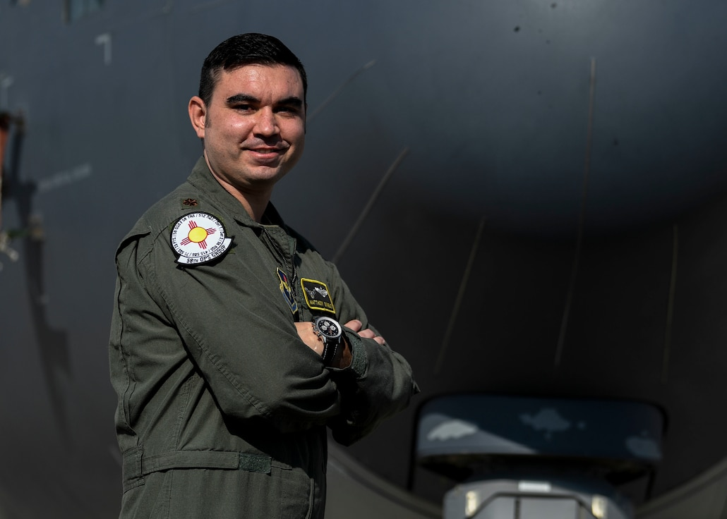 Air Force officer poses in front of large aircraft