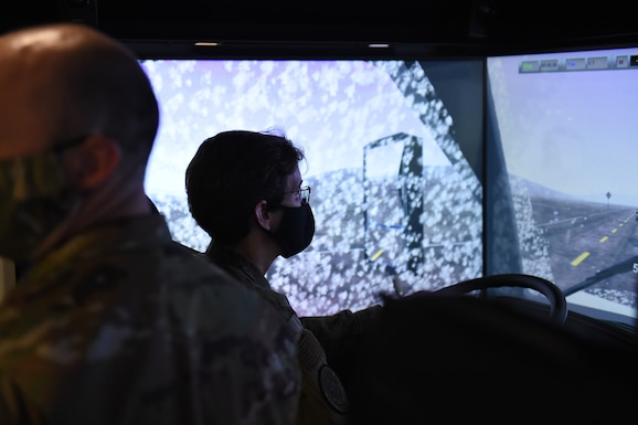 Gen. Jacqueline Van Ovost, Air Mobility Command commander, drives a large vehicle simulator at the 627th Logistic Readiness Squadron on Joint Base Lewis-McChord, Wash.