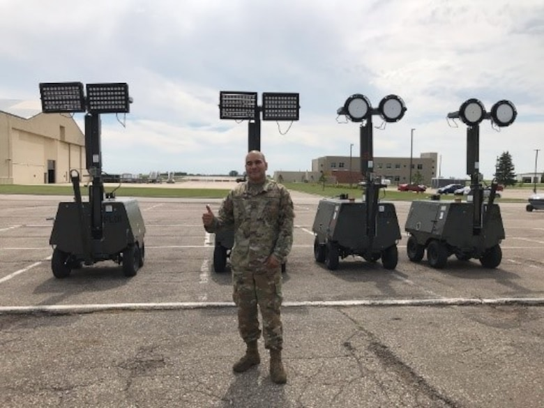 Air Force Global Strike Command 5th Maintenance Squadron AGE Section Chief, Master Sgt. Miguel Alvarez, in front of four flightline light carts retro-fitted with the two different LED fixture options for testing. (U.S. Air Force photo/Senior Airman Matthew Brown)